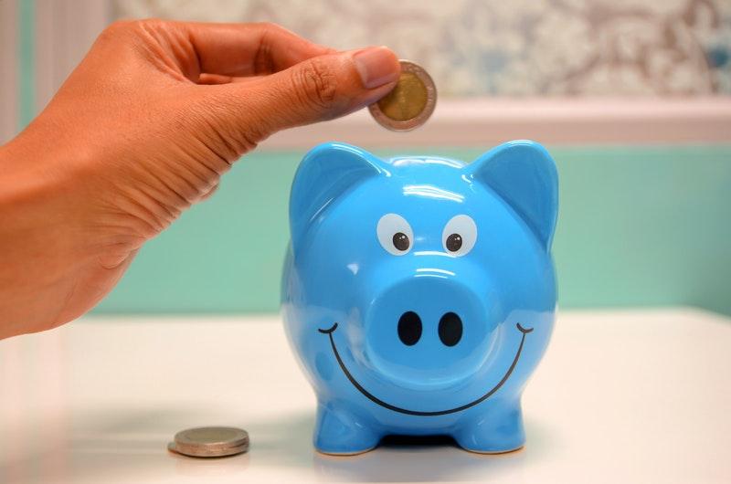 Person Putting Coin Into Piggybank